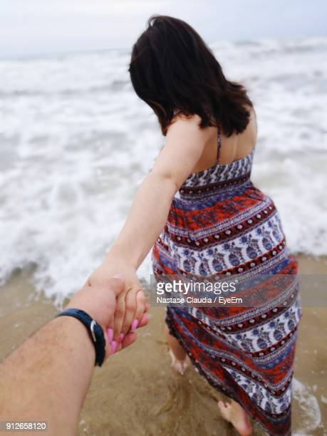 Cropped Image Of Man Holding Woman Hand At Beach
