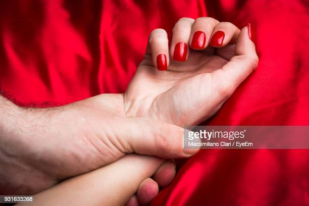 Cropped Image Of Man Holding Woman Hand On Bed