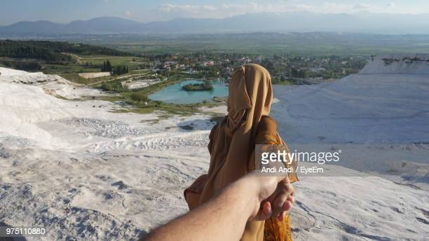 Cropped Image Of Man Holding Woman Hand On Mountain