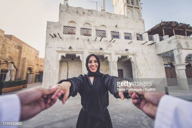 cropped image of man holding woman hands in town - abu dhabi stock pictures, royalty-free photos & images