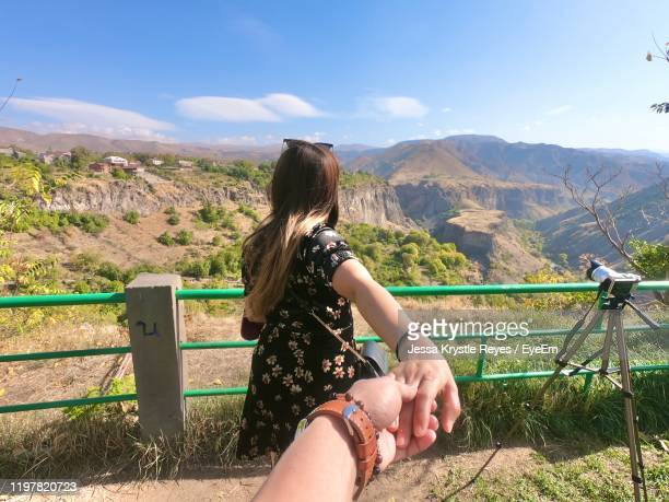 cropped image of man holding woman hands on mountain - jessa stock pictures, royalty-free photos & images