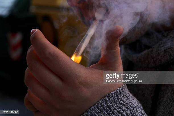 cropped image of man igniting marijuana joint with lighter - drug abuse stock pictures, royalty-free photos & images