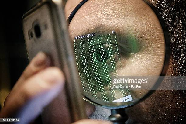 cropped image of man looking at mobile phone through magnifying glass - conspiracy stock pictures, royalty-free photos & images