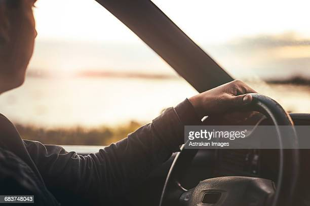 Cropped image of man looking at sunset view while driving car