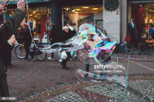 Cropped Image Of Man Making Oversized Bubbles On City Street