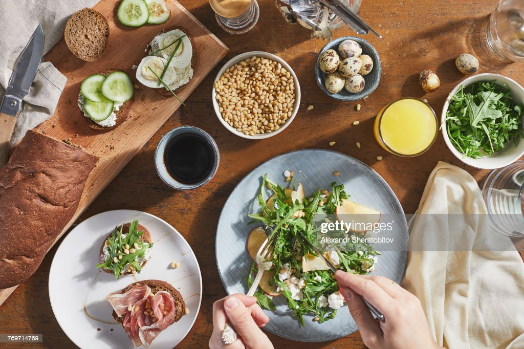 Cropped image of man mixing salad with fork and table knife in plate on table : Stock Photo