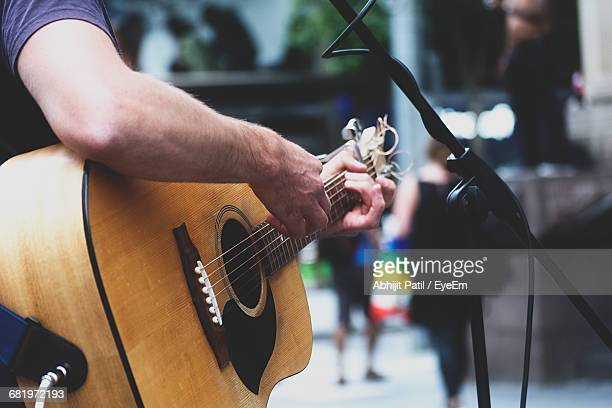 cropped image of man performing with acoustic guitar on street - arts culture and entertainment stock pictures, royalty-free photos & images