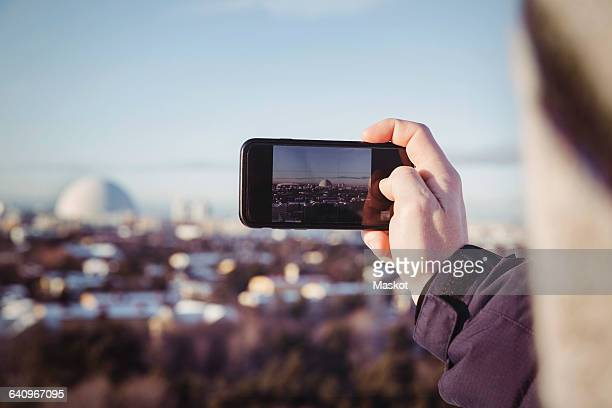 Cropped image of man photographing cityscape through mobile phone during winter