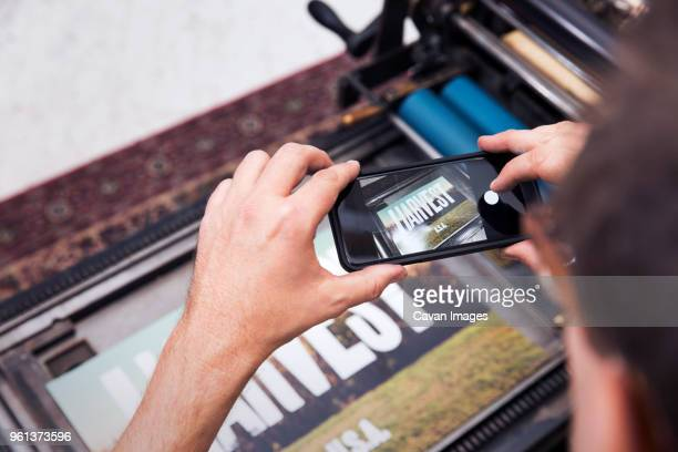 Cropped image of man photographing printed poster with smart phone