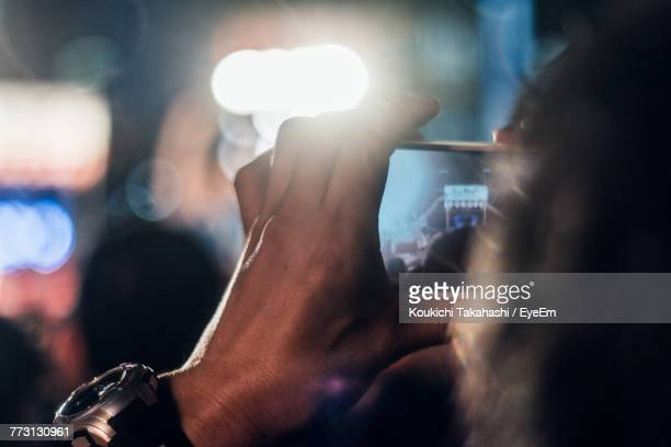 Cropped Image Of Man Photographing With Mobile Phone At Night