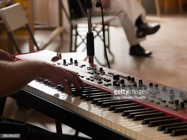 cropped image of man playing electric piano - electric piano stock photos and pictures