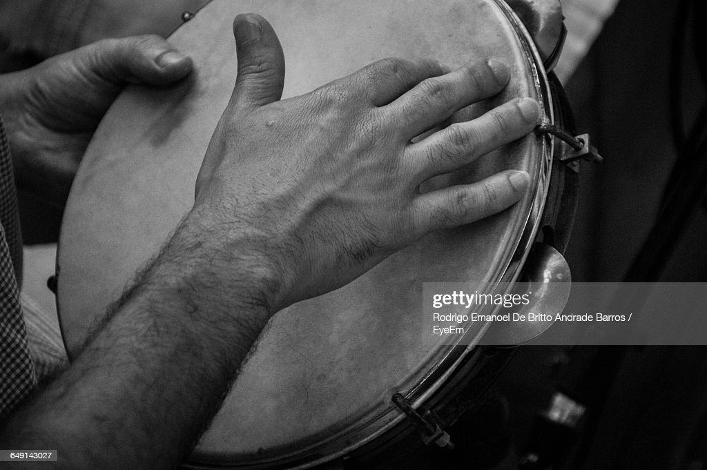 Cropped Image Of Man Playing Tambourine : Stock Photo