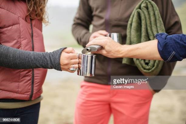 cropped image of man pouring alcohol in woman's mug on beach - flask stock pictures, royalty-free photos & images