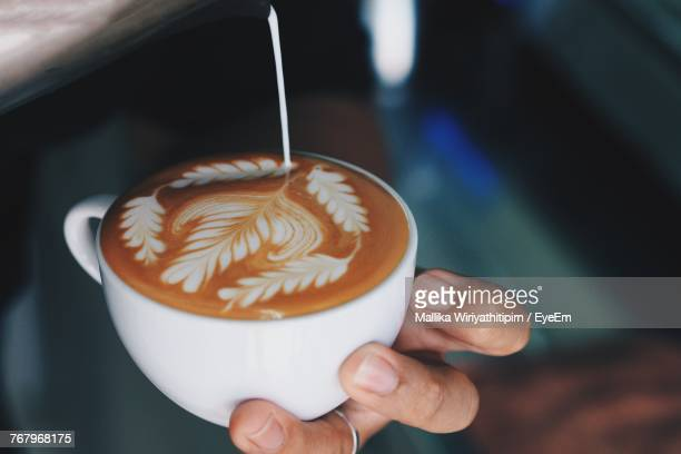 Cropped Image Of Man Pouring Milk On Coffee Cup