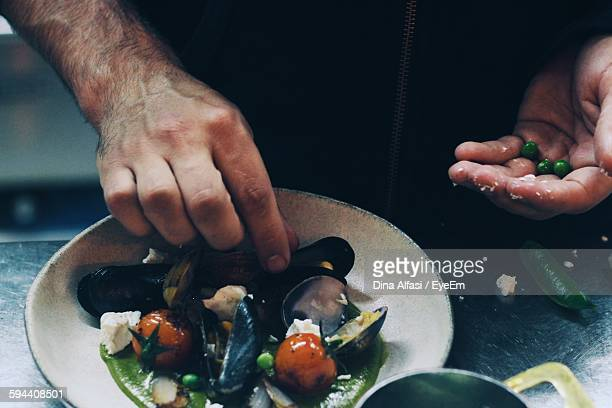 Cropped Image Of Man Preparing Mussel In Container