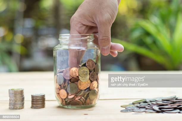 Cropped Image Of Man Removing Coins From Jar