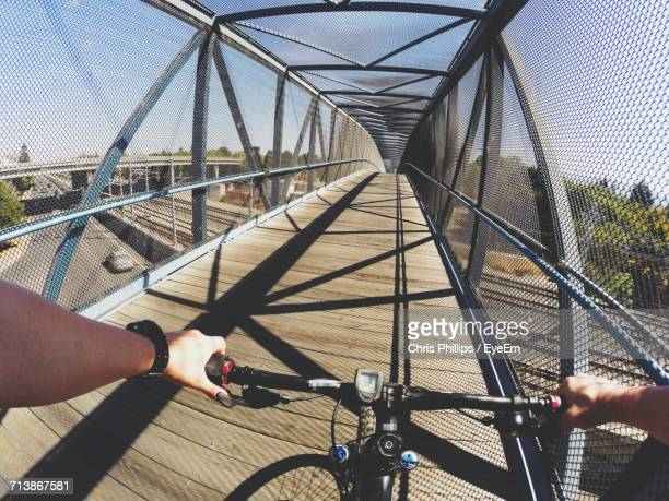Cropped Image Of Man Riding Bicycle On Bridge