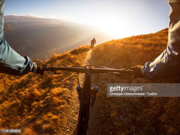 cropped image of man riding bicycle on mountain - standpunt stockfoto's en -beelden