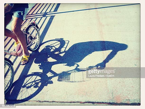 Cropped Image Of Man Riding Bicycle On Street