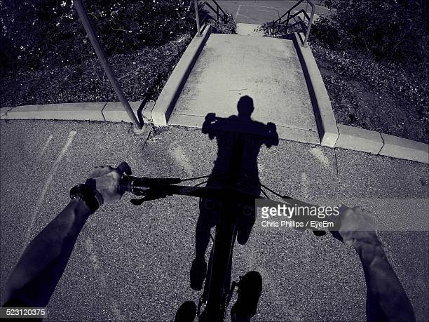 Cropped Image Of Man Riding Bicycle With Shadow On Street