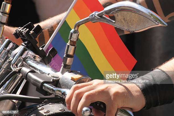 Cropped Image Of Man Riding Motorcycle With Rainbow Flag