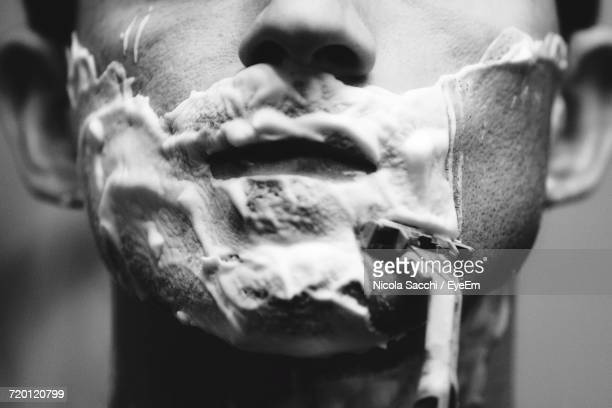 cropped image of man shaving in bathroom - shaving stock pictures, royalty-free photos & images
