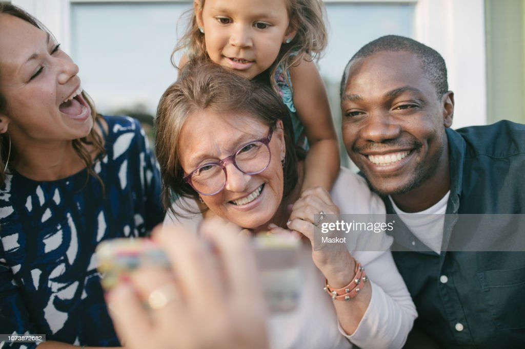 Cropped image of man showing mobile phone to happy family on porch : Stock Photo