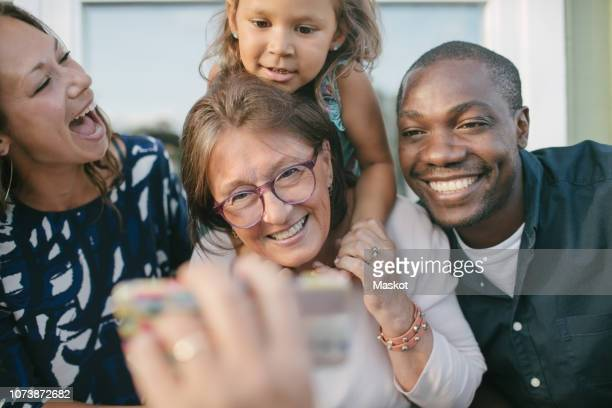 cropped image of man showing mobile phone to happy family on porch - family and happiness and diverse stock photos and pictures