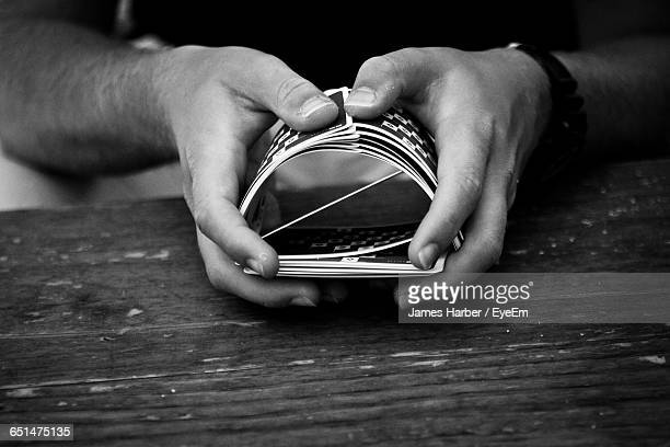 cropped image of man shuffling cards at table - shuffling stock photos and pictures