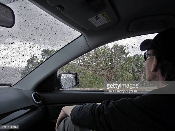Cropped Image Of Man Sitting In Car During Rainy Season