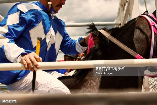 cropped image of man sitting on horse at competition - horse racing stock pictures, royalty-free photos & images