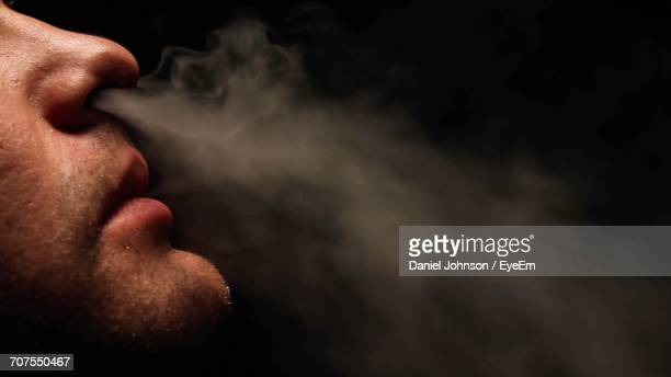 Cropped Image Of Man Smoking Against Black Background