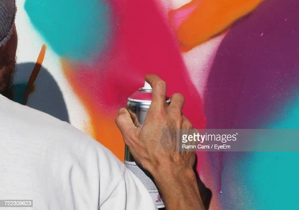 Cropped Image Of Man Spray Painting On Wall