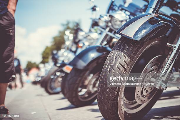 Cropped Image Of Man Standing By Motorcycles Parked On Street