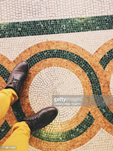 Cropped Image Of Man Standing On Mosaic Flooring