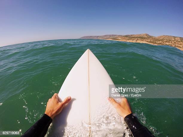 Cropped Image Of Man Surfboarding On Sea