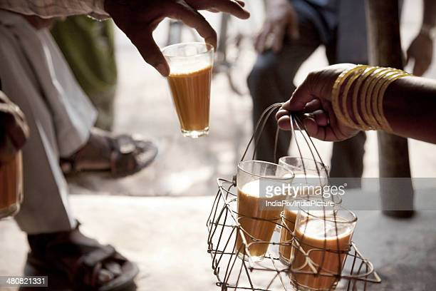 Cropped image of man taking glass of chai from tray held by woman