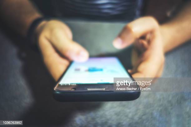 Cropped Image Of Man Using Mobile Phone At Home