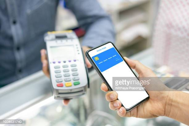 cropped image of man using nfc technology to pay bill at cinema - nfc stock pictures, royalty-free photos & images