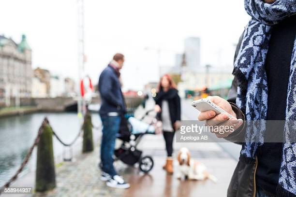 Cropped image of man using smart phone with family in background on sidewalk