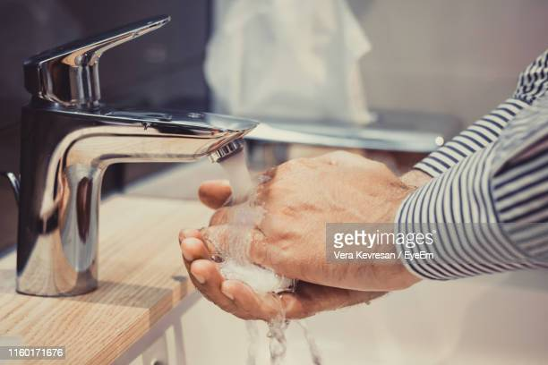 cropped image of man washing his hands in sink - 中央部分 ストックフォトと画像