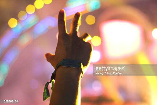 cropped image of man wearing bracelet at concert - bracelet stock pictures, royalty-free photos & images