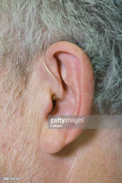 cropped image of man wearing hearing aid - ear canal stock photos and pictures