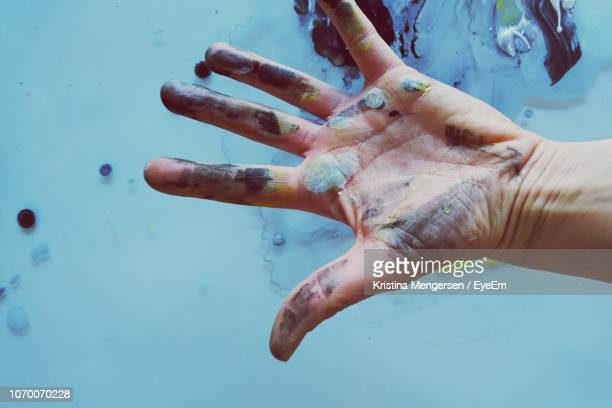 cropped image of man with messy painted hand - pittore foto e immagini stock
