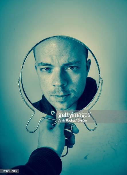Cropped Image Of Man With Reflection On Mirror Against Wall