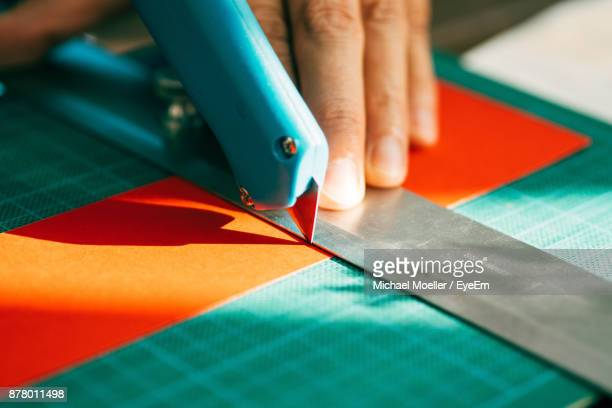 cropped image of man working at table - utility knife stock photos and pictures