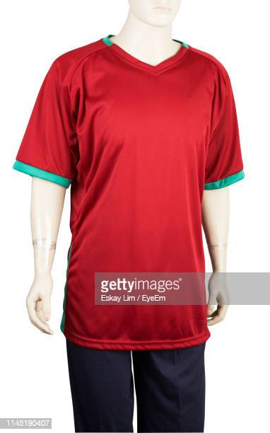 cropped image of mannequin wearing red t-shirt standing against white background - mannelijke gelijkenis stockfoto's en -beelden