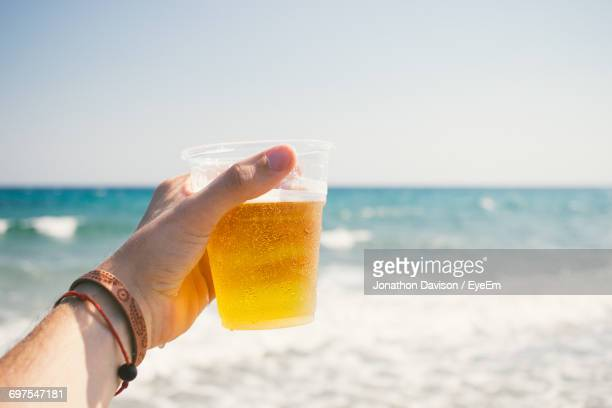 Cropped Image Of Mans Hand Holding Beer Glass At Beach Against Clear Sky
