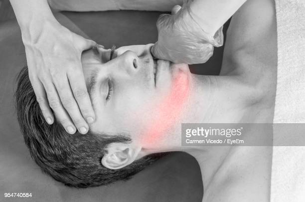 cropped image of masseur massaging man in spa - human mouth stock pictures, royalty-free photos & images