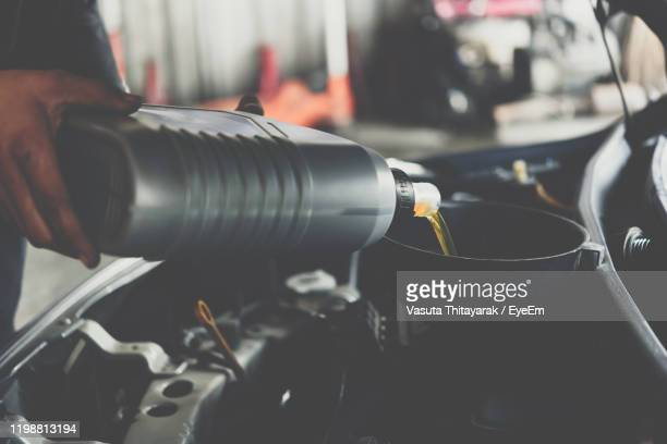 cropped image of mechanic pouring motor oil into car engine - car lubricants 個照片及圖片檔